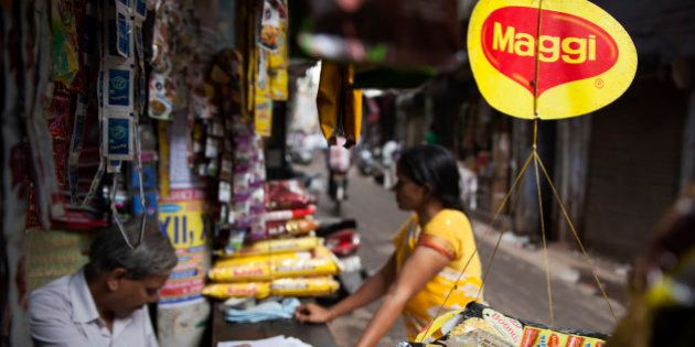 A basket filled with packaged food hangs with a 'Maggi' sign on it outside a shop in New Delhi, India,...