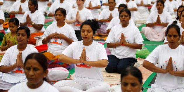 Yoga enthusiasts perform Surya Namaskar or sun salutation as they celebrate World Yoga Day in Bangalore,...