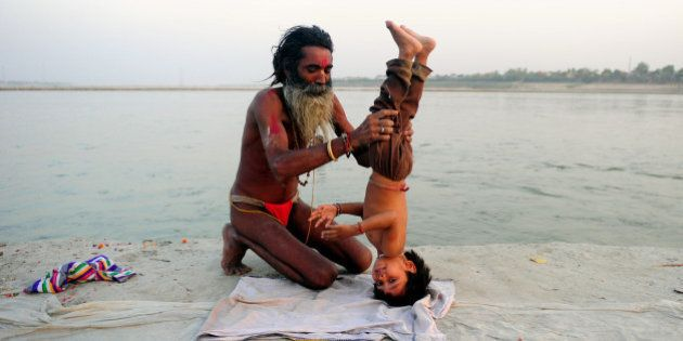 An Indian Hindu Sadhu (holy man) poses his adopted child in a yoga headstand on the banks of the Sangam...