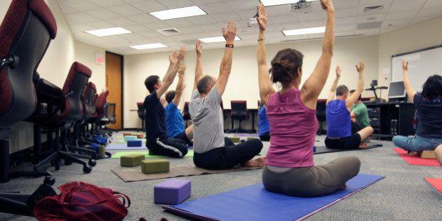 CAMBRIDGE, MA - JUNE 3: Noon office yoga class at Draper Laboratory, one of Draper's employee wellness...