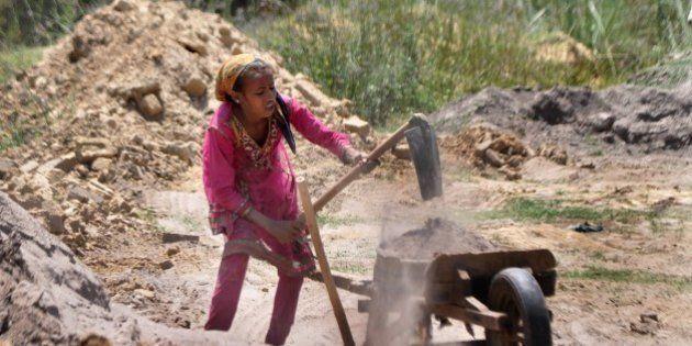 In this photograph taken on June 11, 2015, twelve year old Indian girl, Kavita works at a brick kiln...