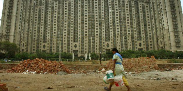 INDIA - APRIL 04: A woman walks past the DLF Ltd. Hamilton court apartment complex in Gurgaon, India,...