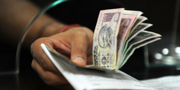 A customer hands over Indian Rupee notes for a deposit to a bank cashier in Mumbai on November 22, 2011....