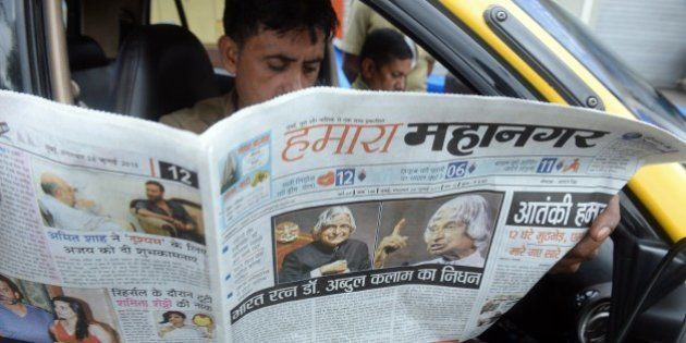 An Indian taxi driver reads a newspaper with the news of the demise of India's former president and top...