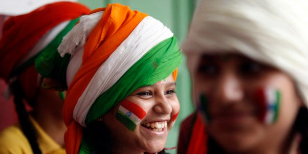 A girl, with her face painted in tricolor Indian flag, smiles as she waits to perform during celebrations...