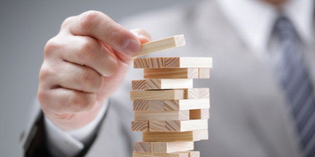 Planning, risk and strategy in business, businessman gambling placing wooden block on a
