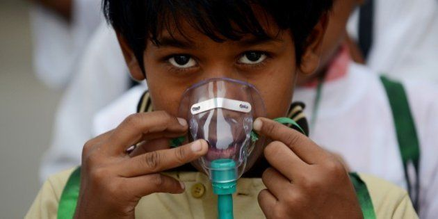 An Indian schoolchild adjusts his facemask before the start of an event to spread awareness of the problem...