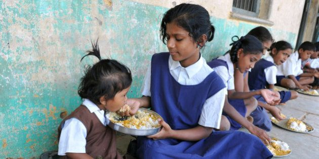 An Indian schoolgirl feeds her younger sister during their mid-day meal at a government primary school...
