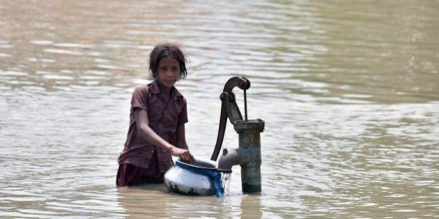 An Indian girl gets water from a partially submerged well in flood-affected Pavakati village, some 70...