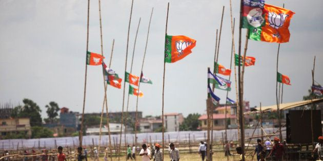 People walk past Bharatiya Janata Party (BJP) flags on bamboo poles in Muzaffarpur, Bihar, India, on...