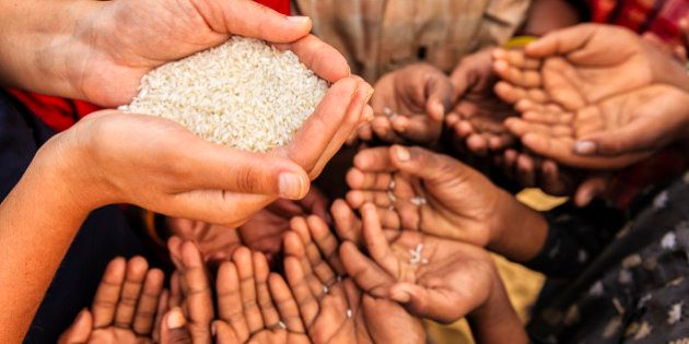 Volunteer caucasian woman giving rice to hungry Indian children. Poor Indian children keeping their hands...