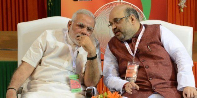 Bharatiya Janata Party (BJP) President Amit Shah (R) talks with Indian Prime Minister Narendra Modi at...