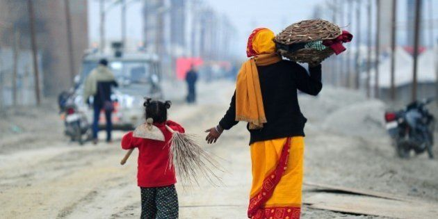 Young Indian child Laxmi (L) carries a broom and hoe as she walks with her mother after working at the...