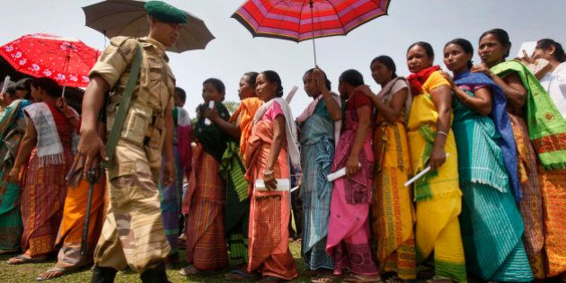 A security guard walks past Bodo tribal women standing in a queue to cast their votes, outside a polling...