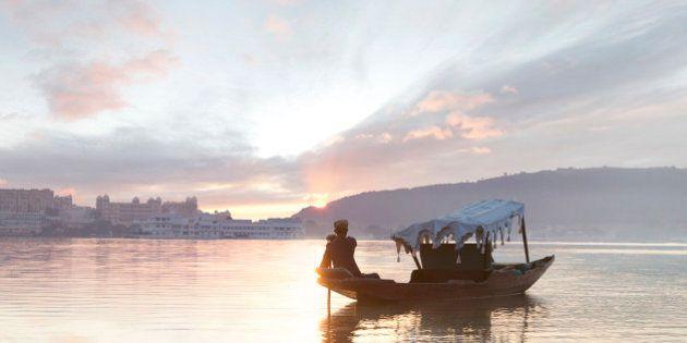 Boat man paddles traditional boat (shikara) in Lake Pichola at