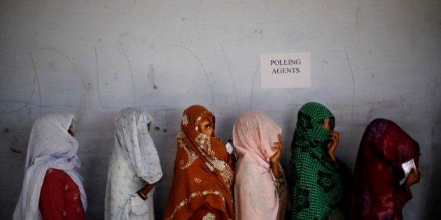 Indian women voters cover their faces as they stand in a queue to cast their votes during a re-polling...