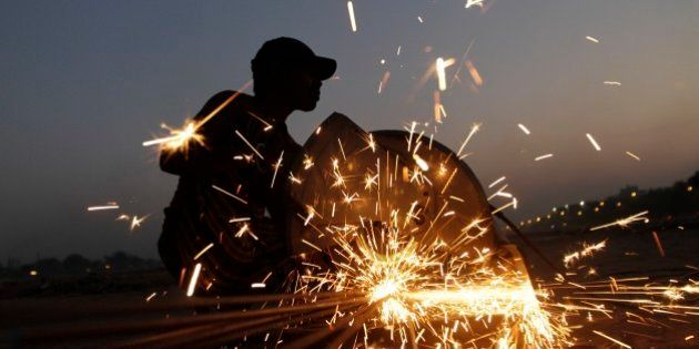 An Indian laborer cuts iron rods at a construction site in Ahmadabad, India, Monday, Feb. 23, 2015. The...