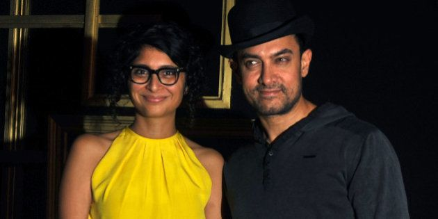 Indian Bollywood actor Aamir Khan (R) poses with his wife Kiran Rao as they arrive to attend a party...