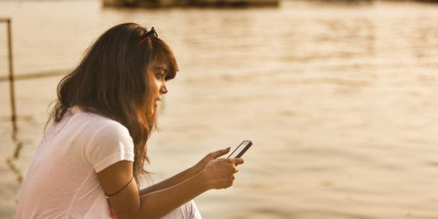 Young woman calling and texting on a mobile