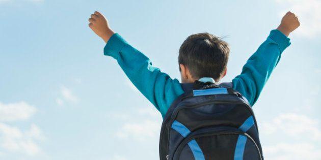 Boy (6-7) wearing backpack punching