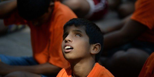 A visually impaired Indian child looks upwards as a ray of sunlight falls on his face while waiting to...