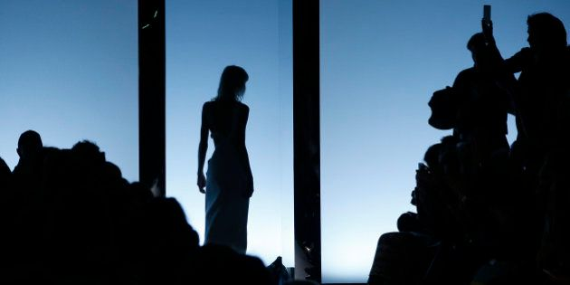A model is silhouetted as she wears a creation for Fausto Puglisi women's Fall-Winter 2016-2017 collection,...