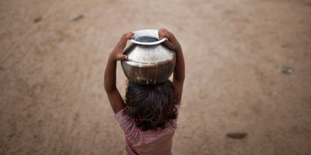 Five-year-old Joshiya, carries a metal pitcher filled with water from a near-by well at Badarganj village...