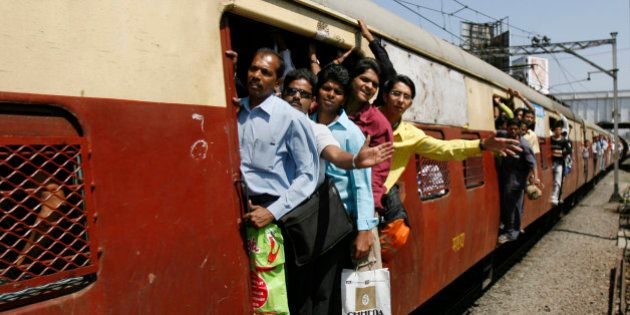 Commuters hang out of the crowded compartments of a local train while travelling in Mumbai February 26,...