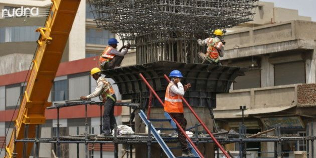 Labourers work at the site of metro railway flyover under construction in Ahmedabad, India, March 31,...