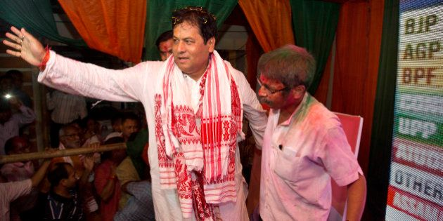 Bharatiya Janata Party, (BJP) leader Sarbanada Sonowal, center, waves to his supporters after party won...