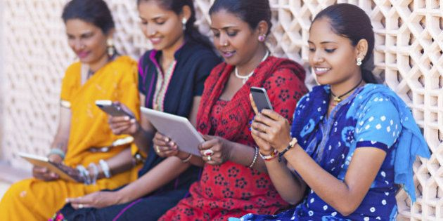 Four indian women playing with digital tablets and smart
