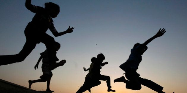 Children play on a sand dune as they are silhouetted against the setting sun in the western Indian city...