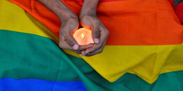 A member of the LGBT community in Bengalaru holds a candle during a memorial service following a mass...