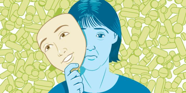 Lots of pills behind woman holding happy mask disguising sad