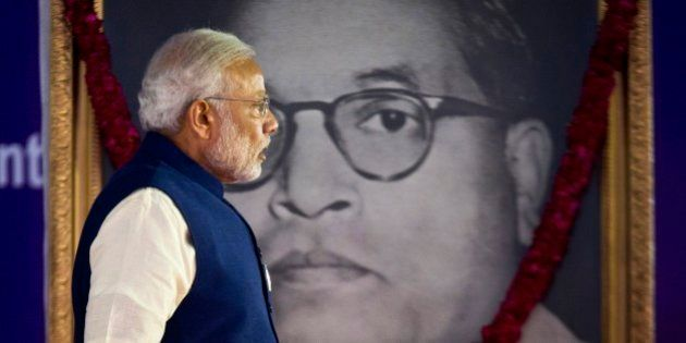 Indian Prime Minister Narendra Modi walks by a photograph of Bhim Rao Ambedkar during the unveiling ceremony...