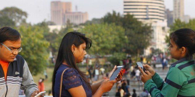 NEW DELHI, INDIA - NOVEMBER 16: Visitors busy on mobile phones after Tata Docomo, the unified telecom...