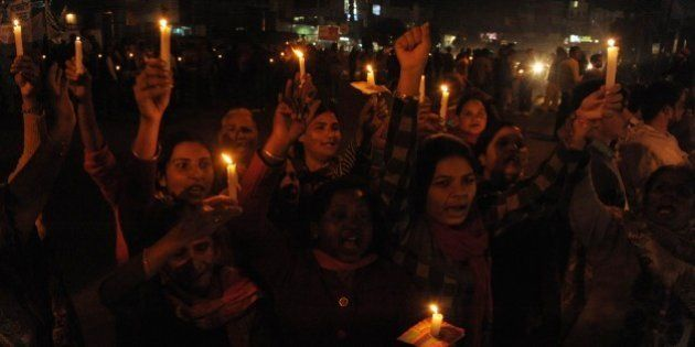 Indian Christian devotees hold candles and chant slogans during a demonstration against a suspected attack...