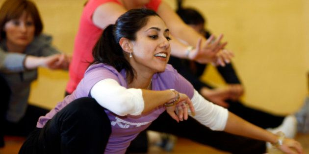 Reflected in a mirror on the walls of the dance studio, instructor Renu Kansal leads students in practicing...