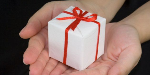 Hands holding a gift box isolated on black