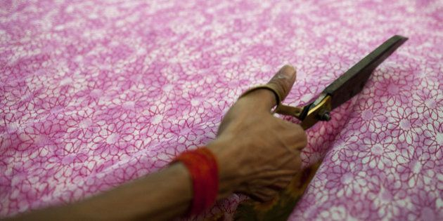 An Indian labourer cuts patterned fabric at the April Cornell clothing factory in Noida on the outskirts...