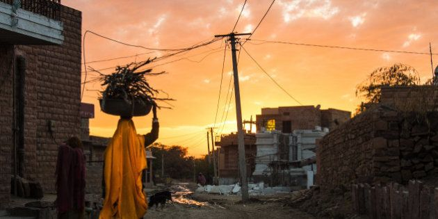 An indian Woman is carrying firewood - a romantic sunset in a less romantic