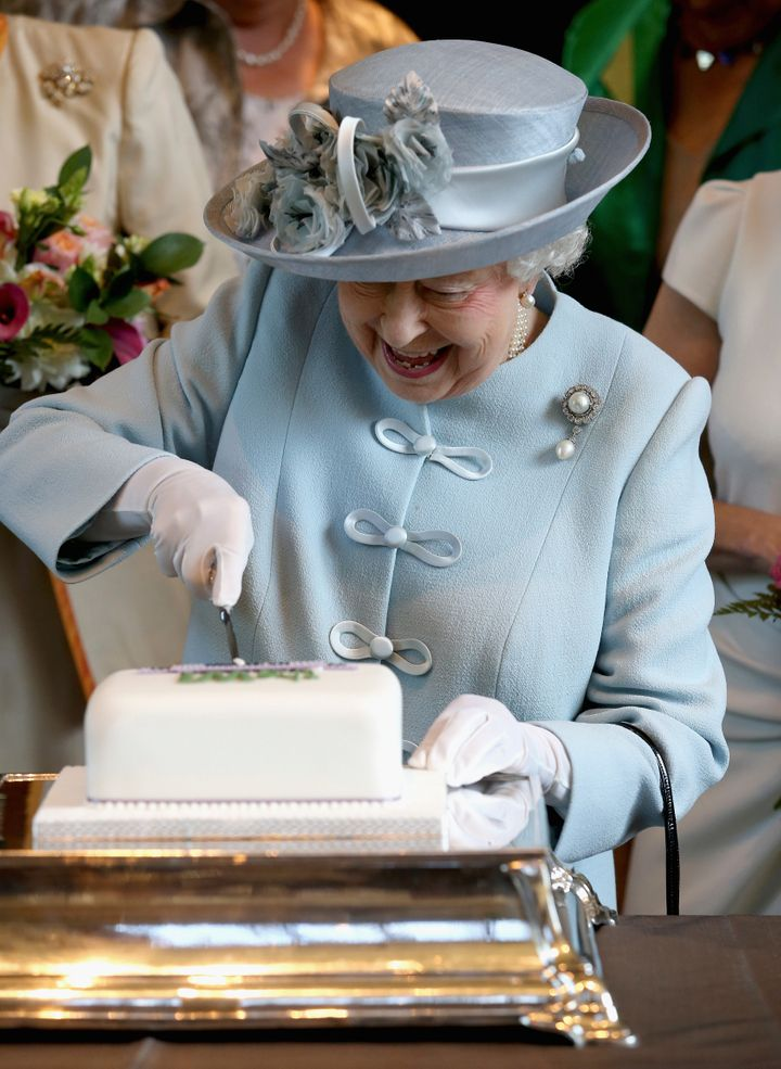 Britain's Queen Elizabeth cuts a Women's Institute Celebrating 100 Years cake at the Royal Albert Hall in London on June 4, 2