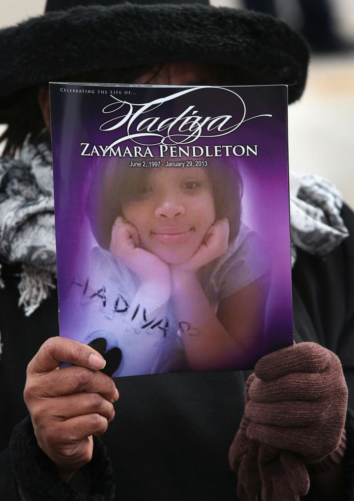 Minister Elnor Brown holds up a funeral program outside the Greater Harvest M.B. Church during the funeral of 15-year-old Had