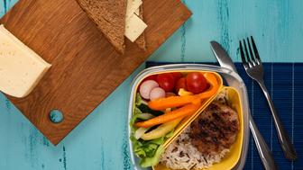 Lunch box with appetizing food and on light wooden table