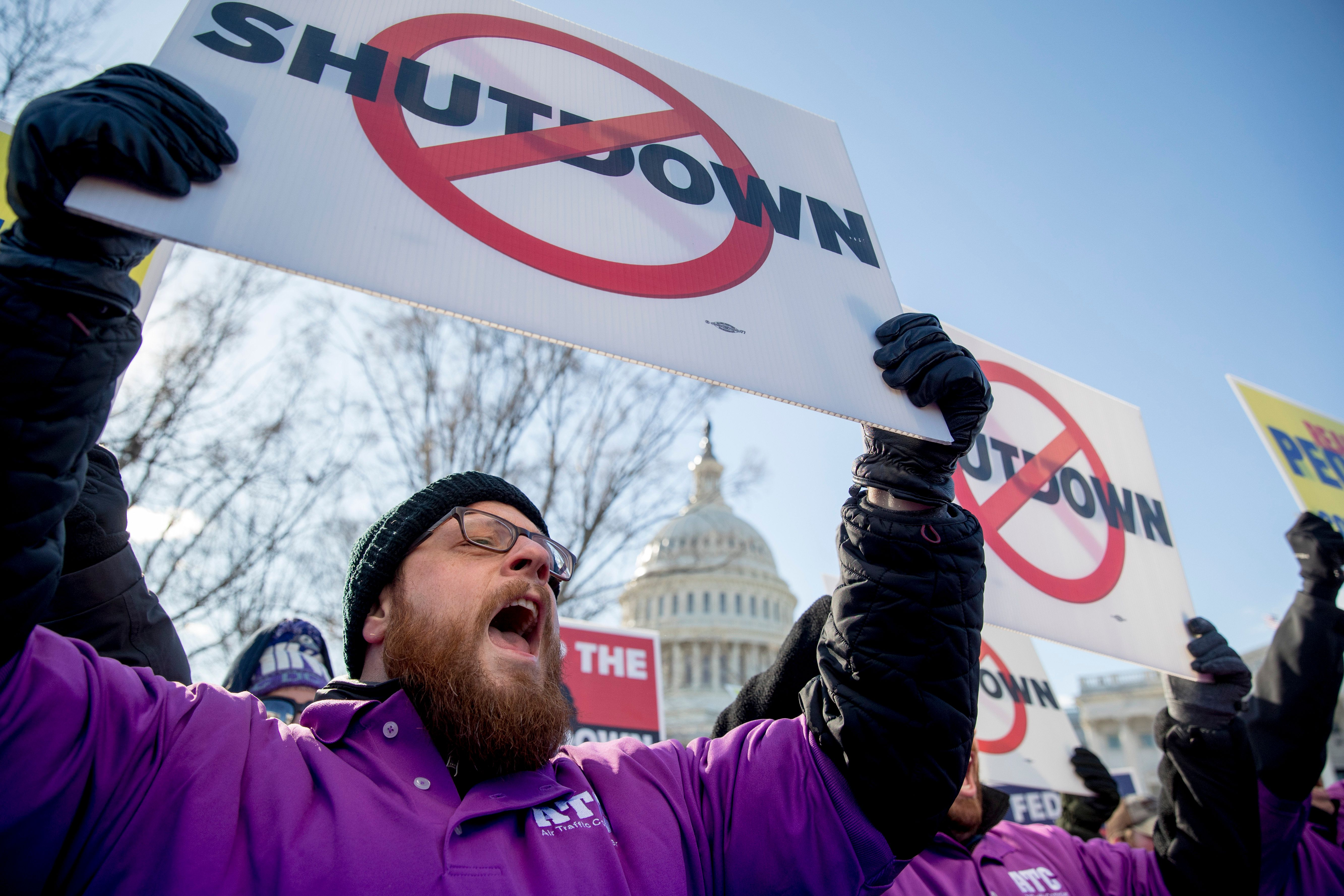 """The Capitol Dome is visible behind Grant Mulkey with the National Air Traffic Controllers Association and others who hold signs and shout in unison to open the government """"NOW!"""" as a call and response as Air Traffic and pilot unions protest the government shutdown on Capitol Hill in Washington, Thursday, Jan. 10, 2019. (AP Photo/Andrew Harnik)"""