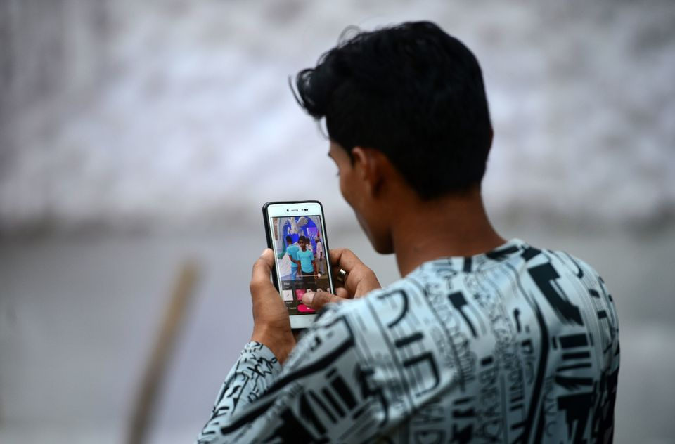 In this photograph taken on October 14, 2018, an Indian man edits a photo on his smartphone in Allahabad. (Photo by SANJAY KANOJIA / AFP)        (Photo credit should read SANJAY KANOJIA/AFP/Getty Images)