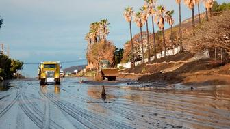 CORRECTS YEAR TO 2019 - In this Sunday, Jan. 6, 2019 photo, California Department of Transportation (CalTrans) crews work to clear mud and rocks that tumbled onto Pacific Cost Highway in Malibu, Calif. In Southern California, light to moderate rain fell early Monday as a second system followed heavy Saturday night downpours that unleashed massive mud flows from the fire-scarred Santa Monica Mountains. Cleanup work kept about 13 miles (21 kilometers) of the scenic highway closed from western Malibu to Ventura County. Caltrans said the closure might last into Tuesday. (Caltrans via AP)