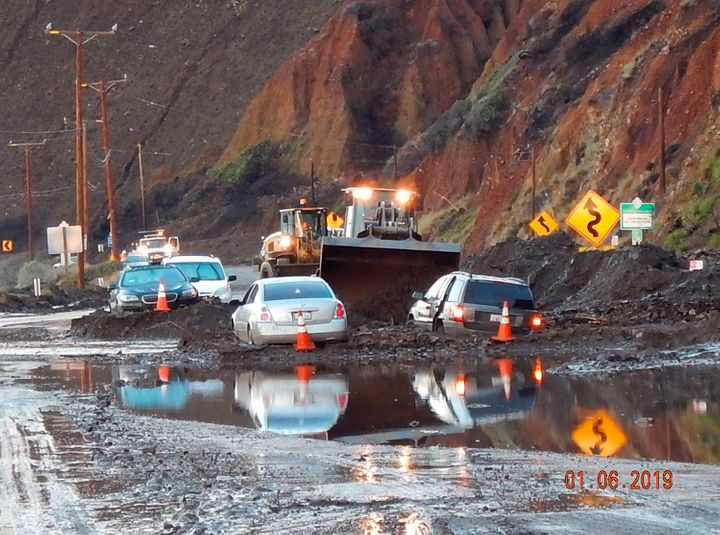 In this Sunday, Jan. 6, 2019 photo, California Department of Transportation (CalTrans) crews work to clear mud and rocks that