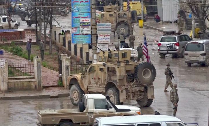 An image grab taken from a video obtained by AFPTV on January 16, 2019, shows U.S. troops gathered at the scene of a suicide