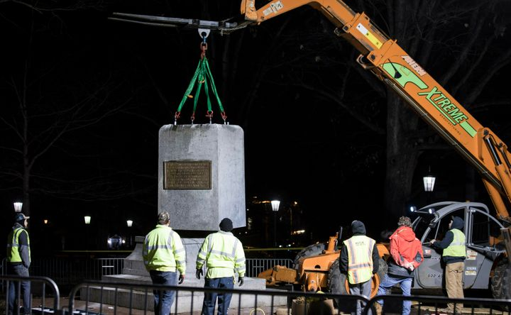 """The remnants of a Confederate statue known as """"Silent Sam"""" is lifted before being transported to the bed of a truck early Tue"""